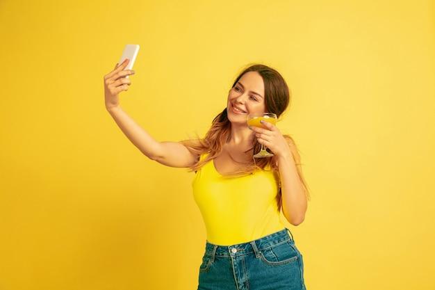 셀카 만들기, 동영상 블로그, 미소. 노란색 스튜디오 배경에 백인 여자의 초상화입니다. 아름다운 여성 모델. 인간의 감정, 표정, 판매, 광고의 개념. 여름철, 여행, 리조트.