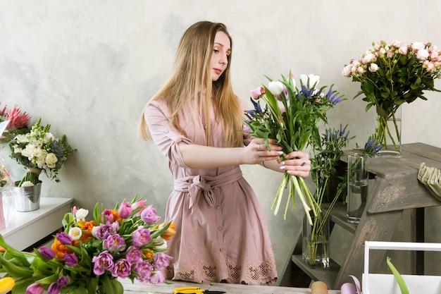 フローリストリーフラワーショップで春の束を作る。白いチューリップ、新鮮な牡丹、野生の花で柔らかい花束を組み立てる花屋。デコレータワークショップ