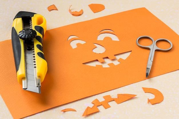 Изготовление трафарета из оранжевой бумаги для канцелярского ножа и ножниц.