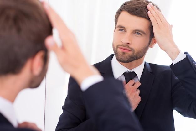 Убедившись, что он выглядит идеально. красивый молодой человек в строгой одежде поправляет прическу и улыбается, стоя перед зеркалом