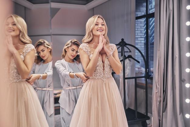 완벽한지 확인합니다. 피팅 룸에 서 있는 동안 신부에 웨딩 드레스를 조정 하는 매력적인 젊은 여자의 반영