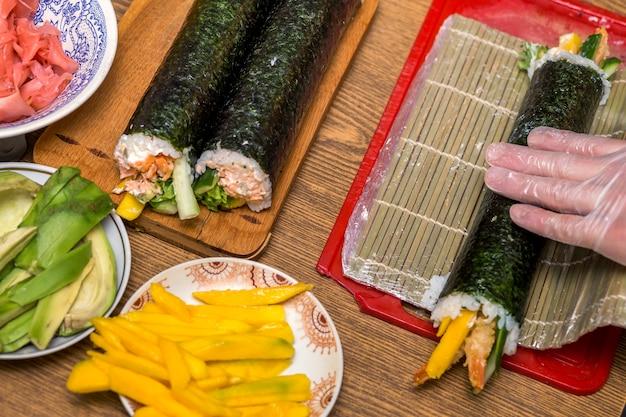 Делаем суши и роллы в домашних условиях. плиты с ингредиентами для традиционной японской кухни и суши роллы на деревянной доске на кухонном столе, вид сверху.