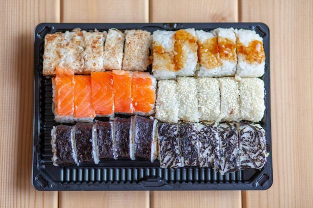 집에서 스시와 롤 만들기. 해산물, 샐러드, 흰 쌀을 곁들인 스시. 가족과 친구를 위한 음식. 트레이에 다른 롤과 스시 세트.