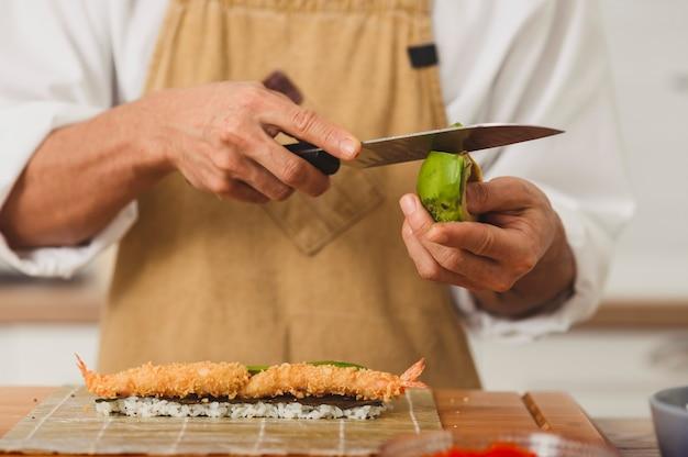 스시 과정을 위한 재료를 준비하는 균일한 껍질을 벗긴 아보카도에서 전문 남성 요리사 만들기