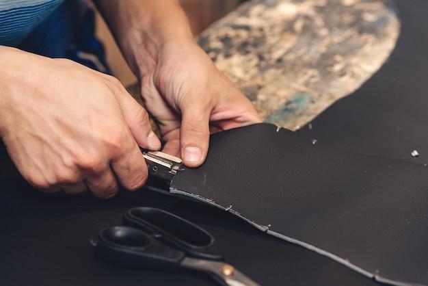 손으로 물건 만들기. 수제 가죽 장인. 작업자 바느질 가죽 제품입니다. 가죽공방. 카시트 커버 봉제 작업 과정. 공예 도구를 들고 작업하는 남자, 닫습니다.