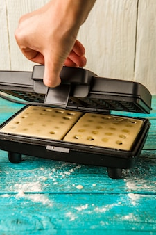 Making waffles at home - batter in waffle iron