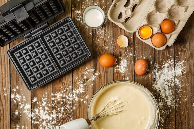 Making waffles at home - waffle iron, batter in bowl and ingredients - milk, eggs and flour.