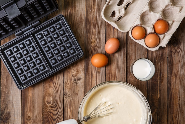 Making waffles at home - waffle iron, batter in bowl and ingredients - milk and eggs.