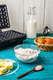 Making waffles at home - waffle iron and ingredients - milk, eggs and flour.