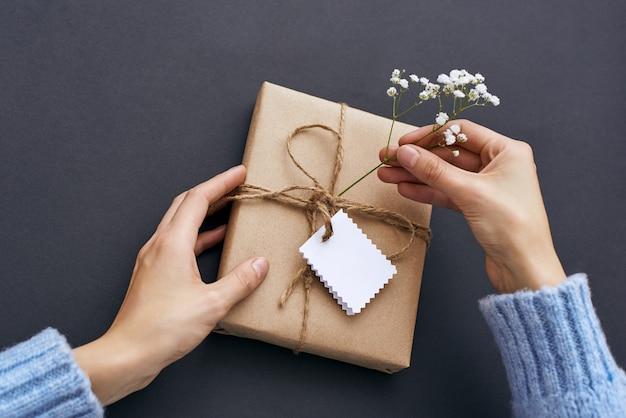 Женские руки держат красивую подарочную коробку и украшают полевыми цветами