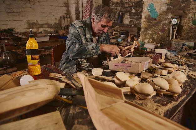 Изготовление деревянных игрушек в мастерской, мастер в действии, старый художник за работой