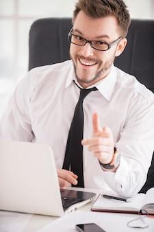 Сделайте ваш бизнес проще. красивый молодой человек в рубашке и галстуке, указывая на вас и улыбаясь, сидя на своем рабочем месте
