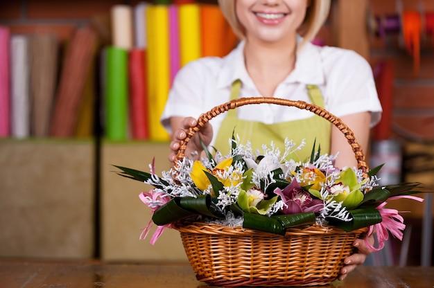 Делает вашу жизнь яркой и красочной. обрезанное изображение молодой женщины со светлыми волосами в фартуке, протягивая корзину, полную цветов и улыбаясь