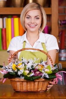 Делает вашу жизнь яркой. привлекательная молодая женщина со светлыми волосами в фартуке, протягивая корзину, полную цветов и улыбаясь