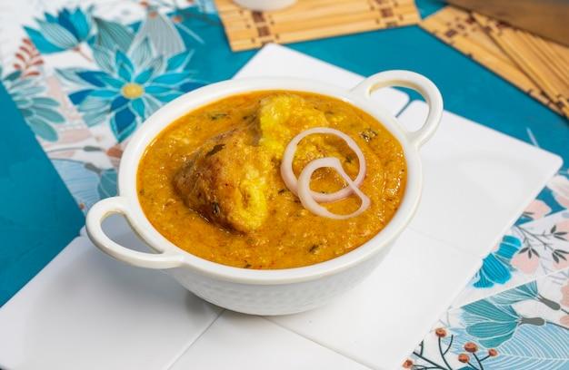 Малай кофта карри на миске на белом фоне. малай кофта - известное блюдо индийской кухни с картофелем, паниром и сыром, обжаренными во фритюре, в луково-томатном соусе с пряными индийскими специями.
