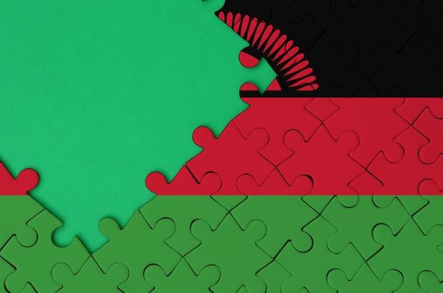 말라위 국기는 왼쪽에 무료 녹색 복사 공간이있는 완성 된 직소 퍼즐에 그려져 있습니다.