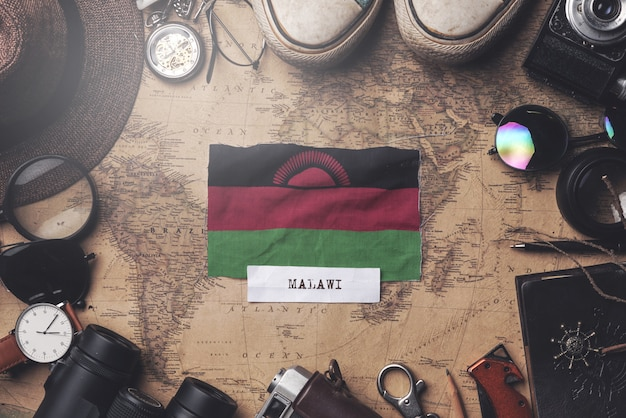 Malawi flag between traveler's accessories on old vintage map. overhead shot