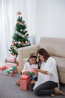 Малайская семья пытается вместе открыть свои рождественские подарки дома