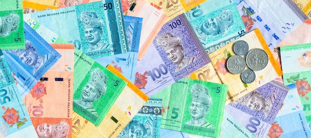 Malaysia currency of malaysian ringgit banknotes and coins background. sen coins of five, ten, twenty and fifty on paper money of one, five, ten, twenty, fifty and hundred ringgit notes.