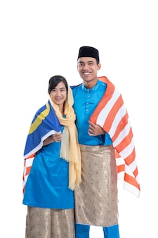 Malaysia flag. couple wearing muslim traditional clothes happy over white background