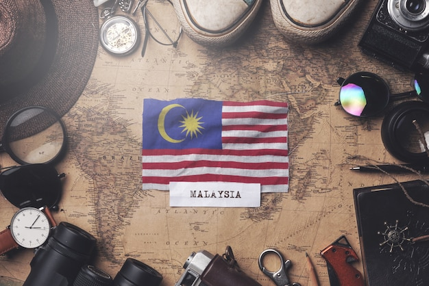 Malaysia flag between traveler's accessories on old vintage map. overhead shot