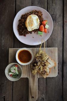 나무 배경에 땅콩 소스를 곁들인 말레이시아 음식 치킨 사테