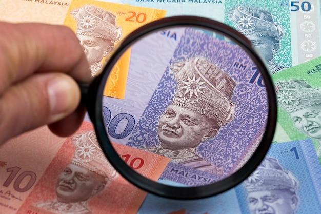 Малайзийские деньги в увеличительном стекле бизнес-фон