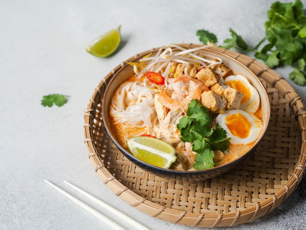 Malaysian noodles laksa soup with chicken, prawn and tofu in a bowl on grey surface. copy space