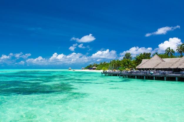 몰디브 워터 방갈로는 섬 해변에서 리조트입니다. 인도양, 몰디브. 아름다운 바다 풍경, 고급 리조트 및 하늘. 멋진 하늘 아래 해변
