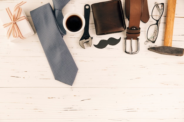 Male accessories near gift and cup of drink
