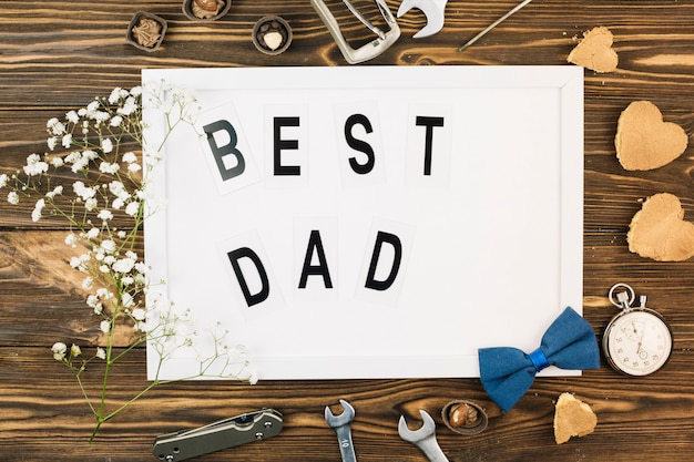 Male accessories near photo frame with best dad title and plant