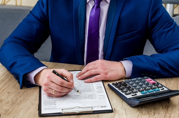 Male accountant filling 1040 tax form