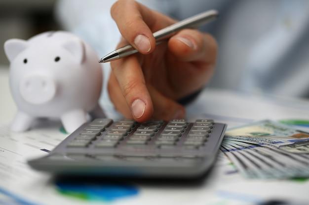男性の会計士はオフィスで給与を数えています