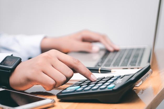 男性の会計士が計算を行い、職場で財務チャートやグラフのデータを確認します。ビジネス財務の概念。