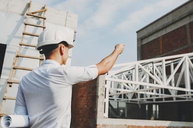 건설중인 건물에 아침에 작업을 시작하는 위치를 보여주는 남성 성인 arhitect.