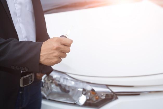 양복과 그의 손에 자동차 키를 들고 남성 성인 사업가