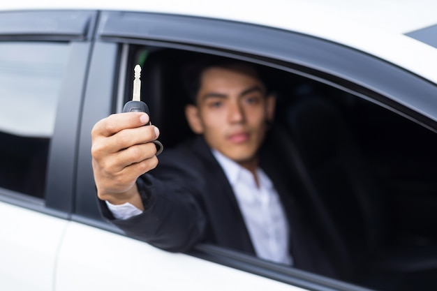 Male adult businessman in a suit  and holding a car key in his hand