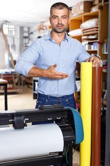 プリンターで立っている色紙のロールを持つ男性の広告スタジオの労働者