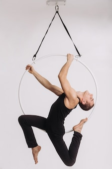 Male aerial gymnast performs acrobatic element in the ring