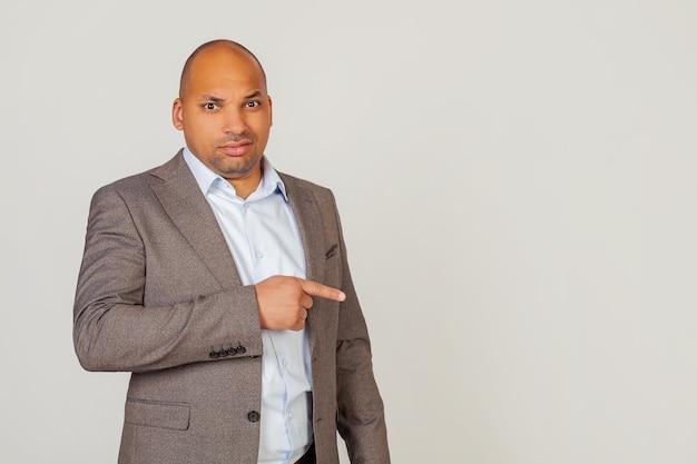 Афро-американский бизнесмен мужского пола в куртке, указывая рукой и пальцем с выражением отвращения. скопируйте пространство. на сером фоне.