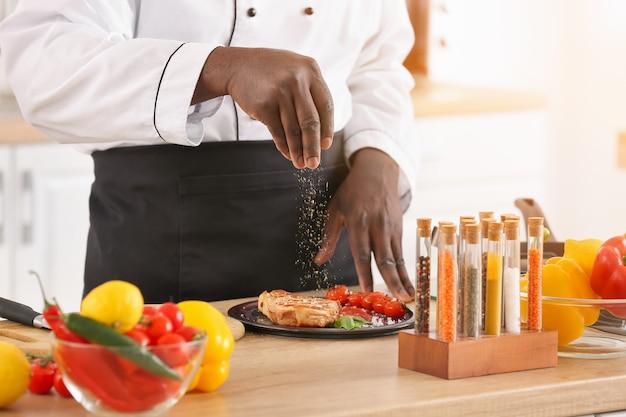 Афро-американский шеф-повар мужского пола готовит на кухне, крупным планом