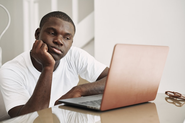 Male african american freelancer with laptop at home
