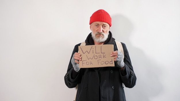 Male aged tramp, homeless old man with a gray beard in a coat and red hat with a sign for help in his hands, isolated white background