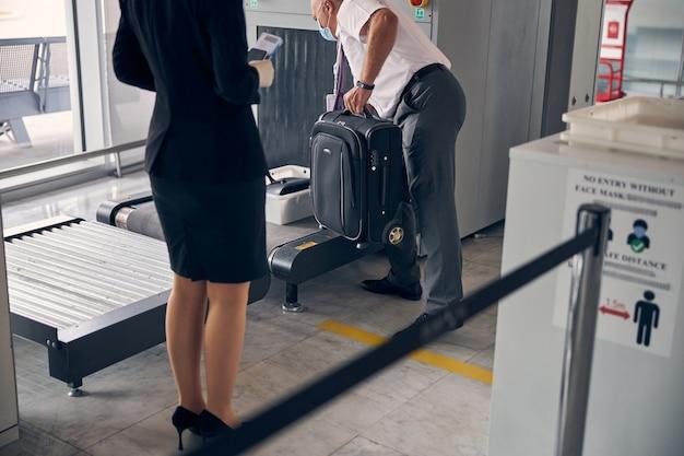 セキュリティチェック中に手荷物コンベヤーベルトに旅行スーツケースを置く医療フェイスマスクの男性空港労働者