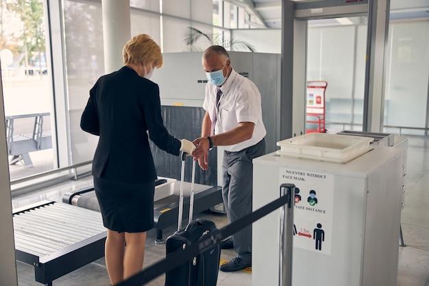 金髪の女性から旅行スーツケースを取る医療フェイスマスクの男性空港労働者
