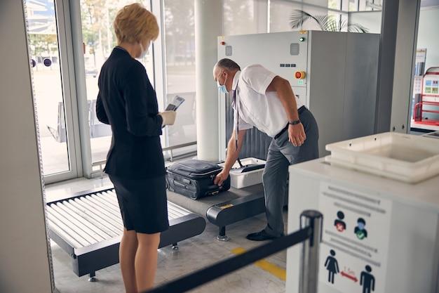 女性が飛行機のチケットを保持している間、手荷物コンベヤーベルトに旅行スーツケースを置く医療マスクの男性空港労働者
