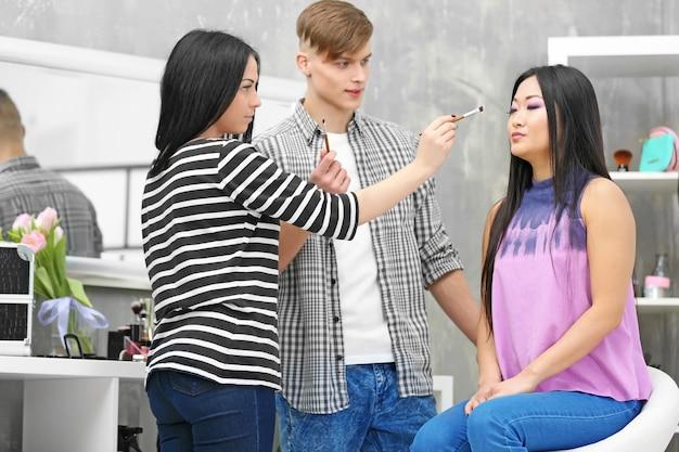 サロンでモデルのメイクをしている男性と女性のアーティスト