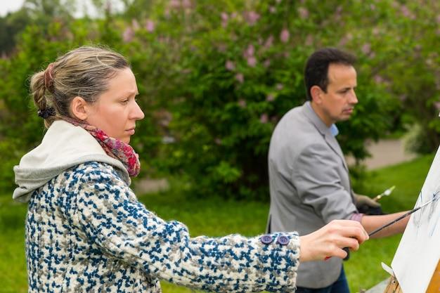 庭でのアートクラスで油絵の具とアクリル絵の具で絵を描くスケッチブックの前に立っている男性と女性のアーティスト
