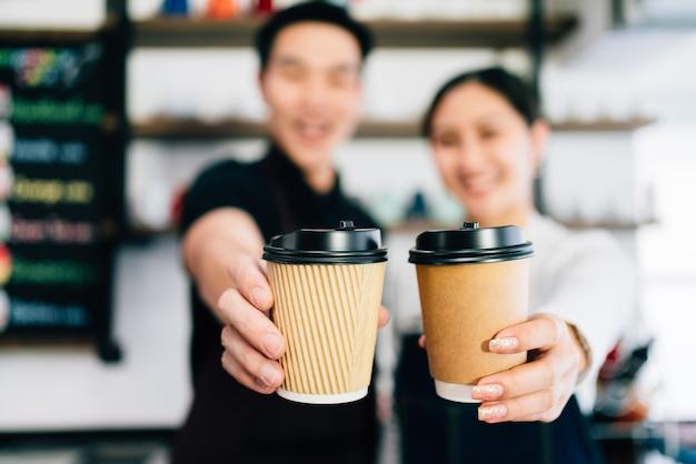 持ち帰り用の紙の使い捨てカップでコーヒーを提供する男性と女性のバリスタ