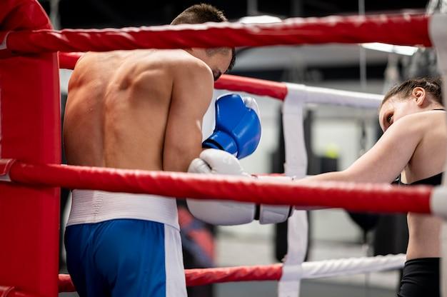 男性と女性のボクサーがリングでトレーニング